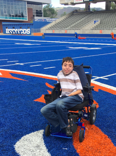 A student poses on the blue turf