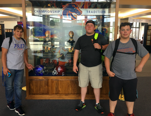 Three students pose by a Bronco trophy case