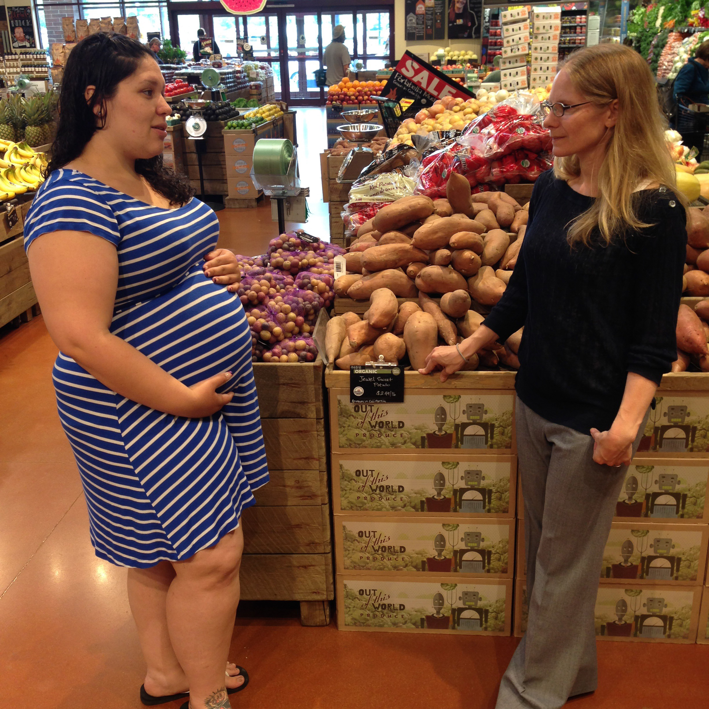 Photo of Curl and Lopez (pregnant) speaking in grocery store