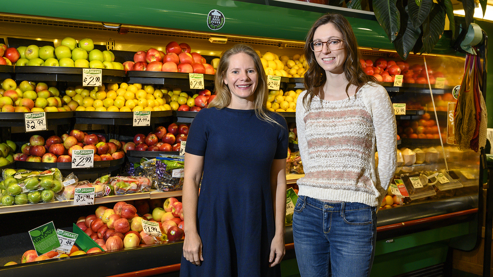 Two women stand in front of produce
