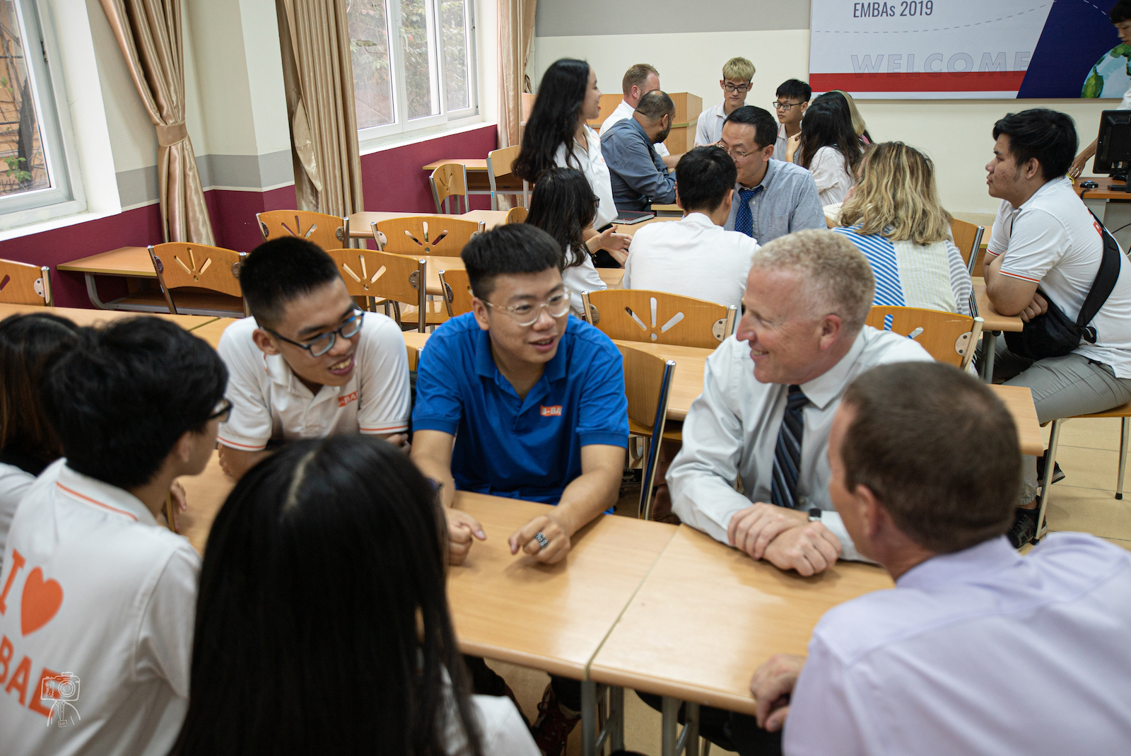 Executive MBA participants Brian Shields and Shannon Boroff visit with Vietnamese students.