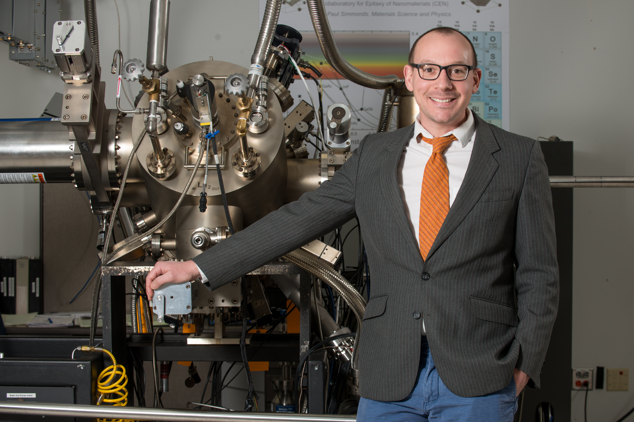 Photo of Simonds standing in front of Molecular Beam Epitaxy apparatus