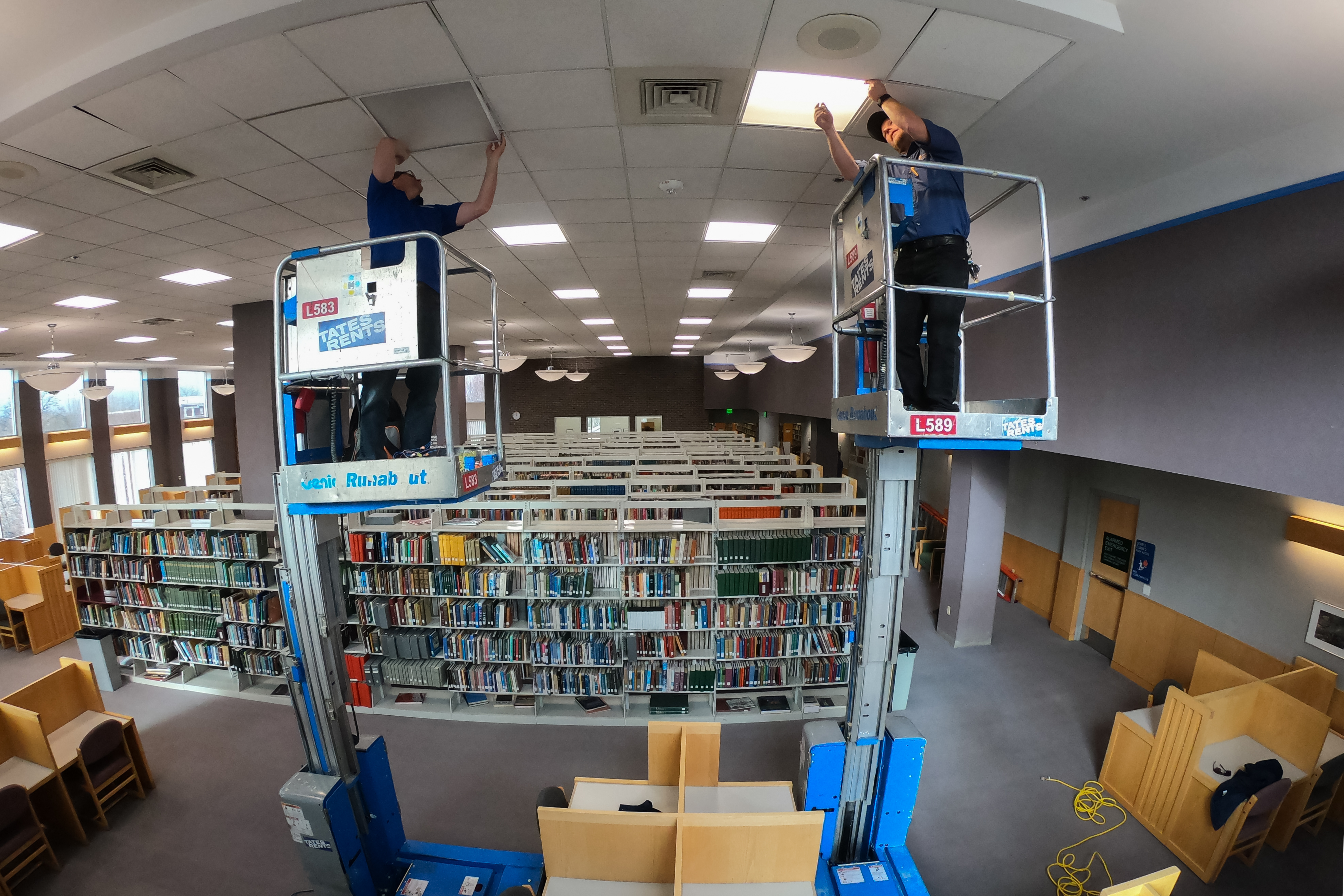 Workers install LED light fixtures