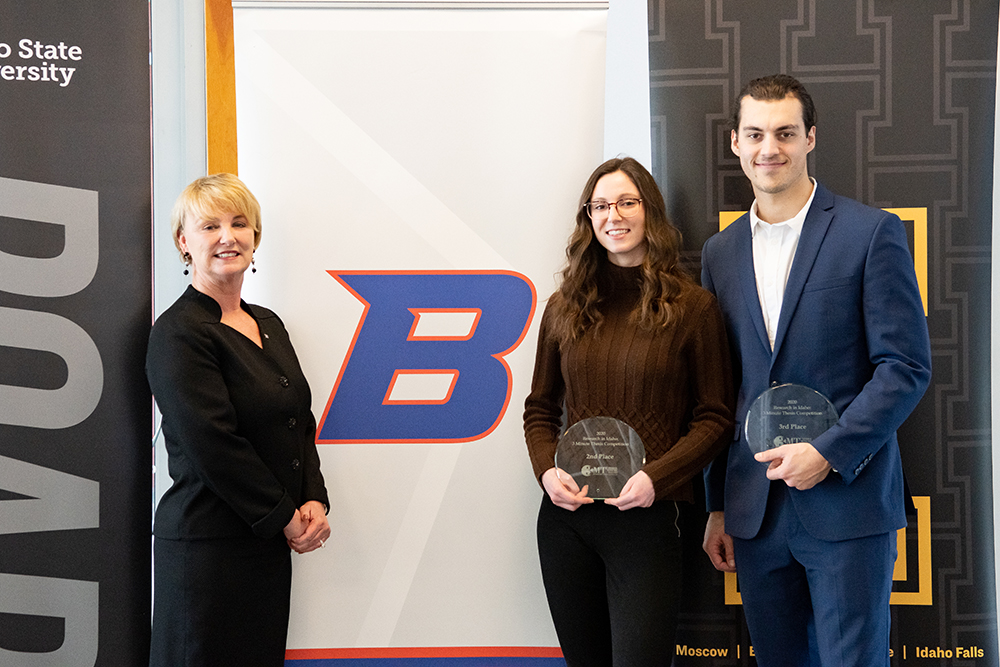Dean and winning students stand with awards