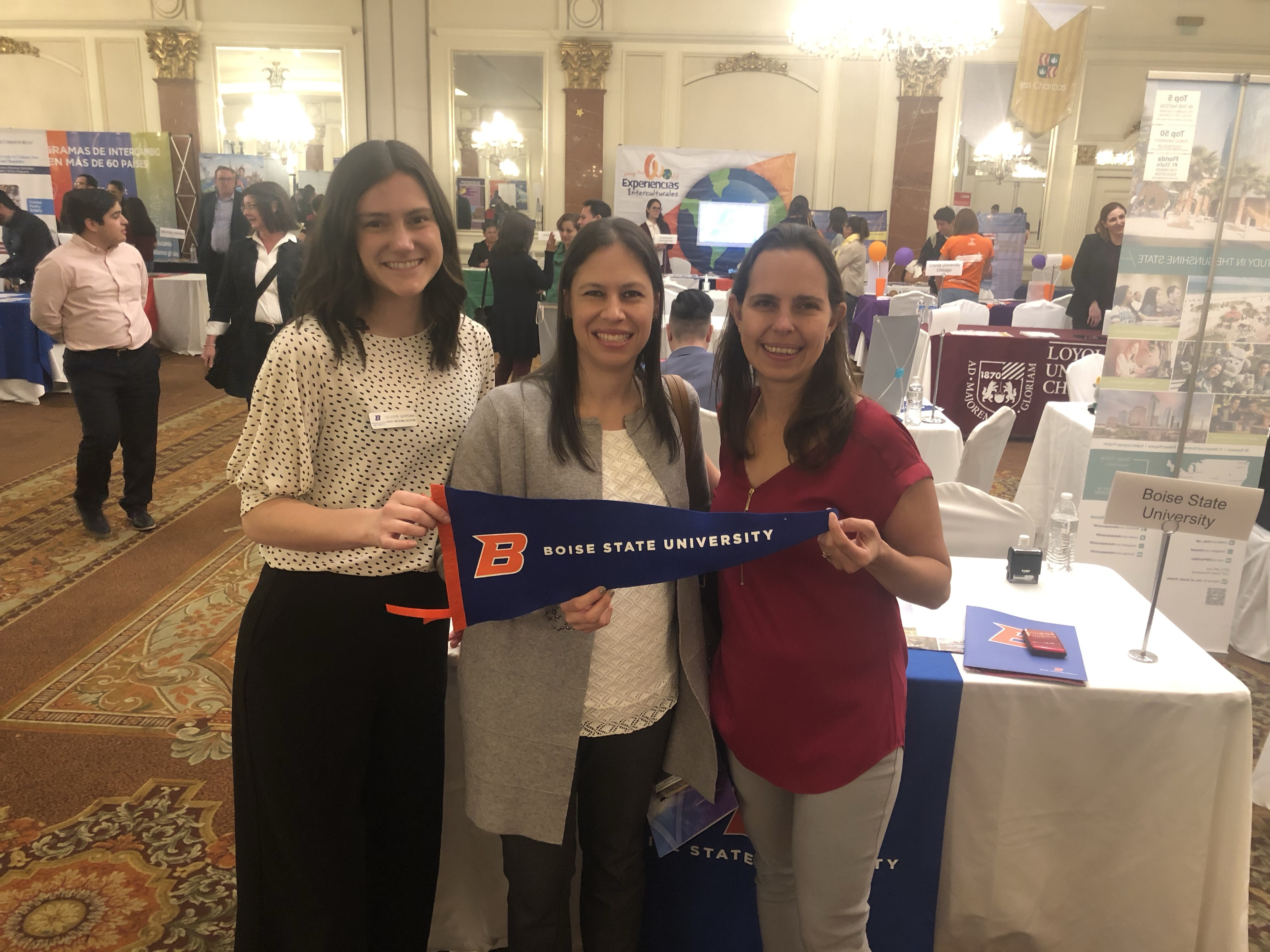 Three women standing side by side holding Boise State banner