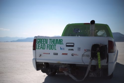 """A truck that says """"green thumb, lead foot"""" on back."""