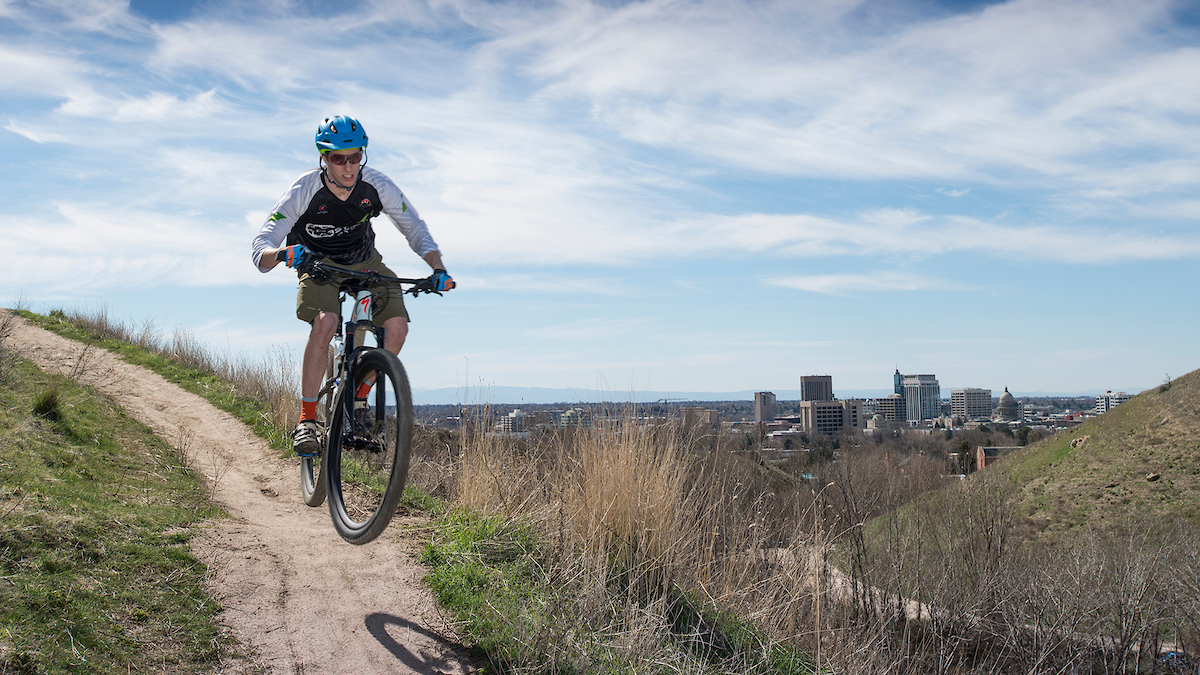 person riding mountain bike on trail, downtown Boise in the background
