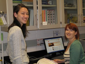 Two students smiling to the camera in their research lab