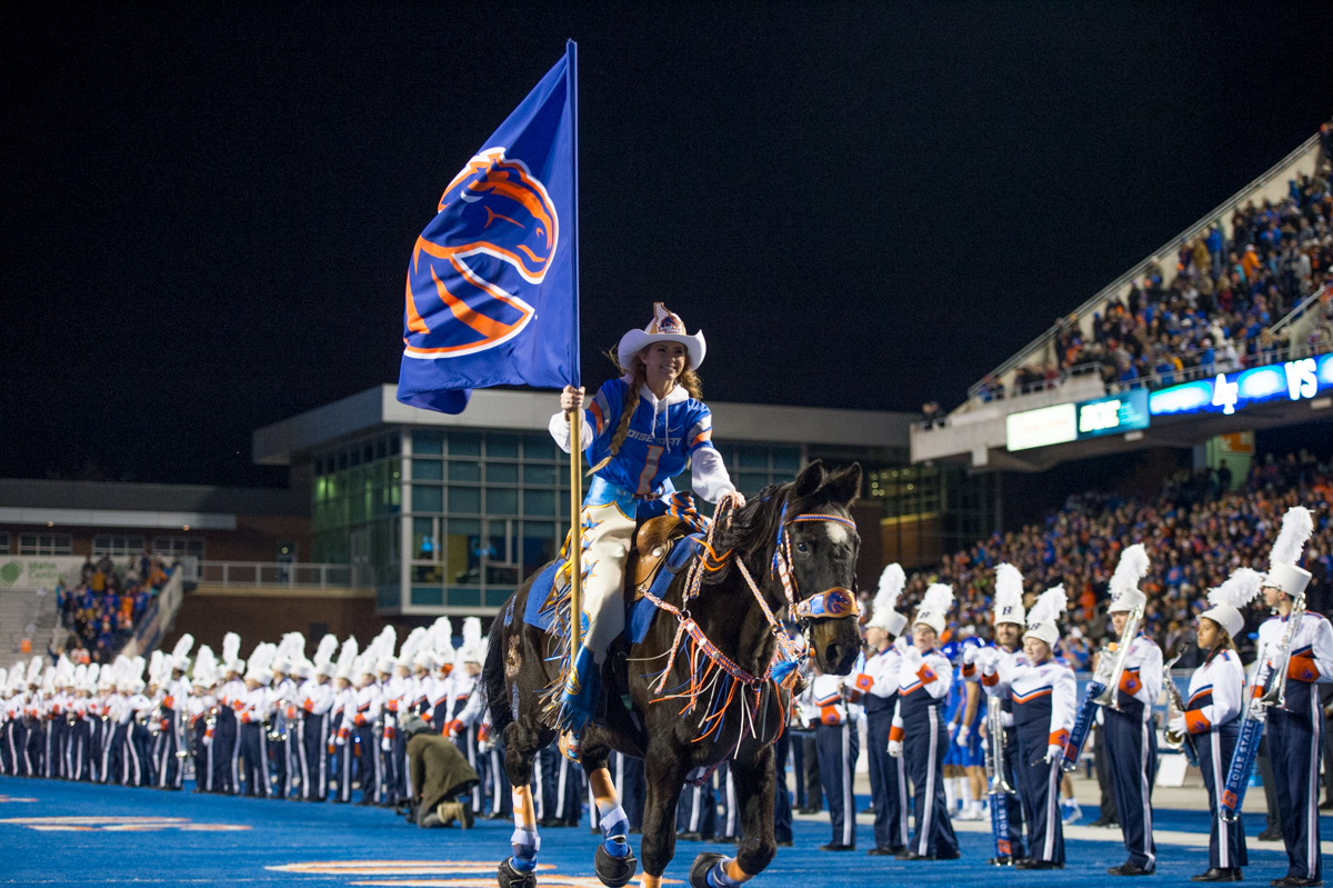 Student on horseback carrying Bronco Athletics flag at football game