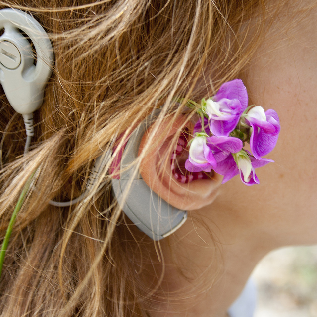 Close-up on a young white woman's cochlear implant. She has tucked some bright pink sweet pea flowers behind her ear.