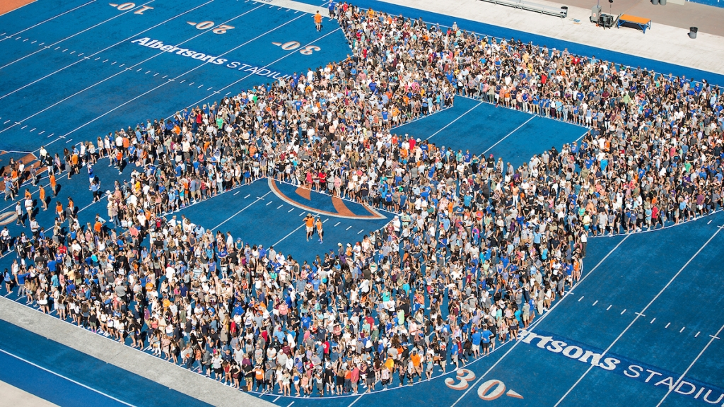 People on blue turf making the B logo