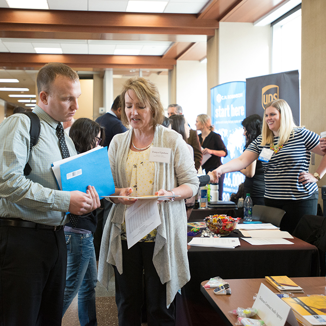 An employer looking over a students resume during COBE career fair