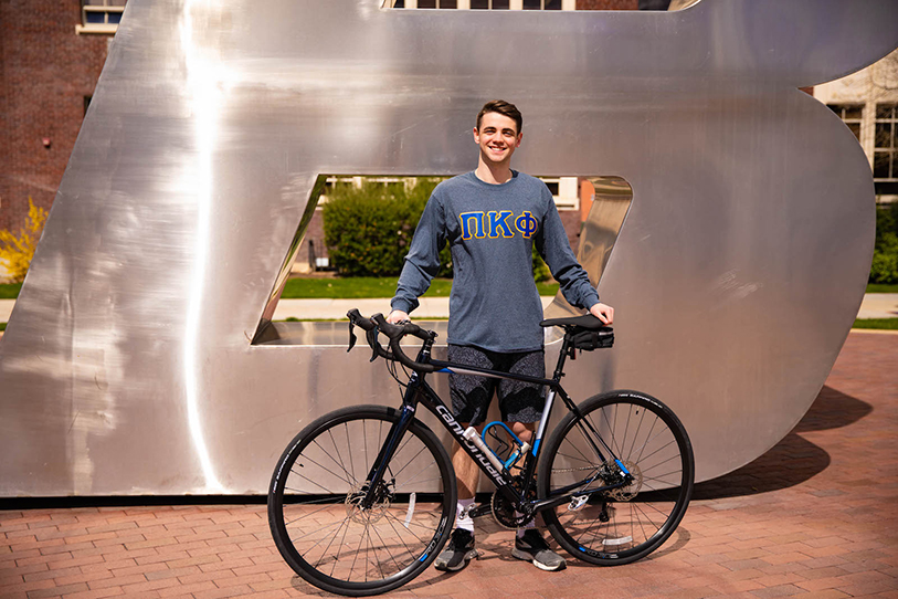 Cole Cunningham with his bike in front of B sculpture