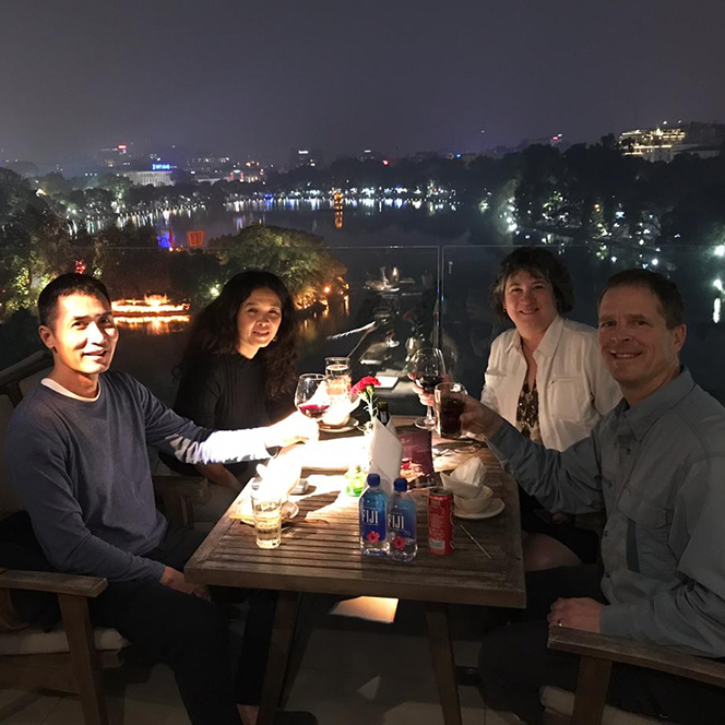 Jonathan and Kim Krutz at dinner with lights of hanoi in the background