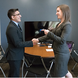 IIvan Sanchez, COBE student, shaking hands with Kelsey White, Deloitte