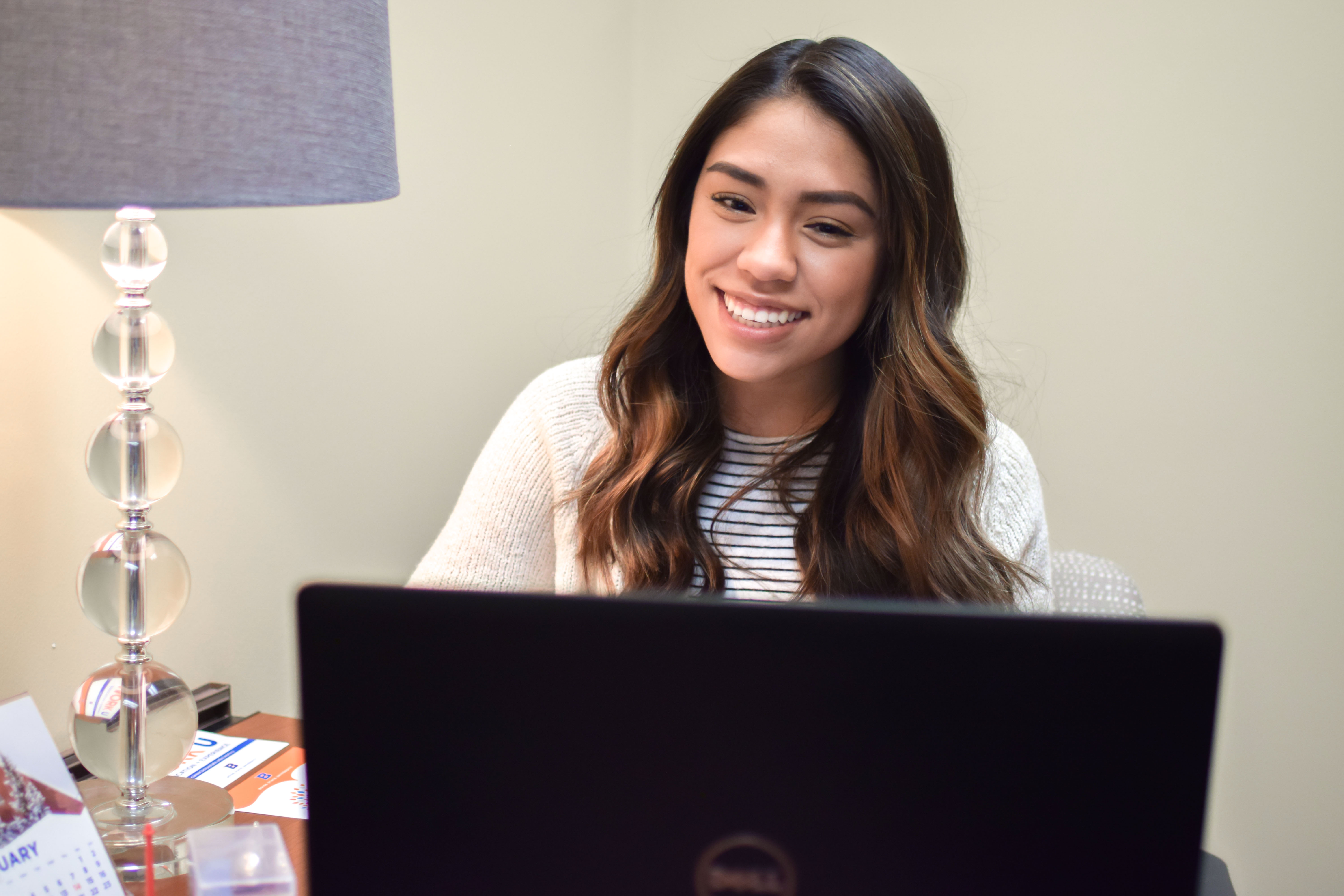 Student looking at laptop and smiling, participating in an online video appointment with a career counselor