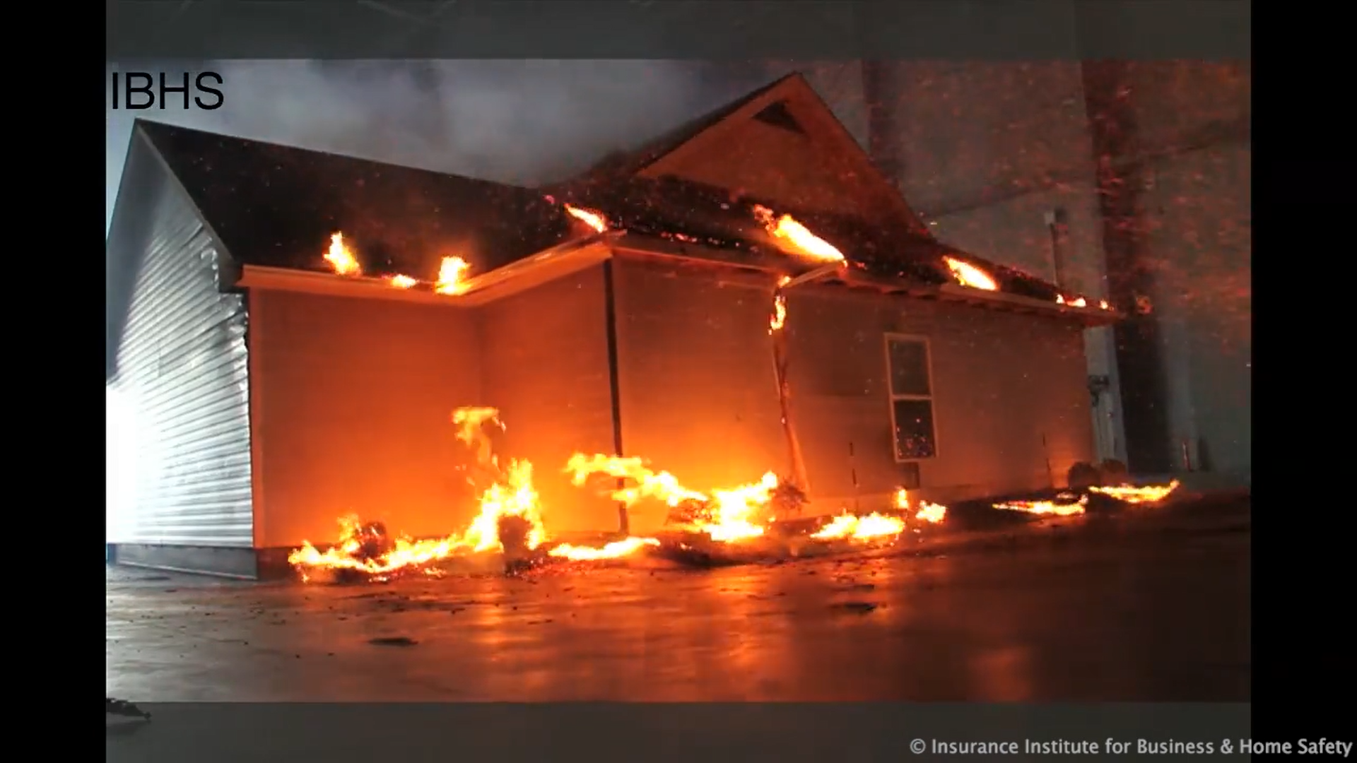A full-size model house catching fire in an airborne-embers experiment. The points of ignition are where dry kindling has accumulated, such as the gutters and the mulch around the house.