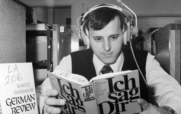 A student listening to the German language through headphones in a language lab.