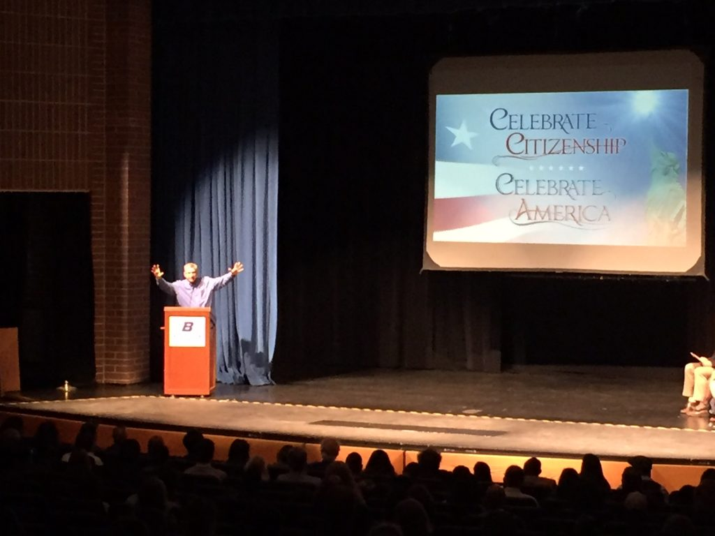 John Ysursa stands at a podium on stage, in front of a crowd of people. Screen behind him reads: Celebrate Citizenship, Celebrate America
