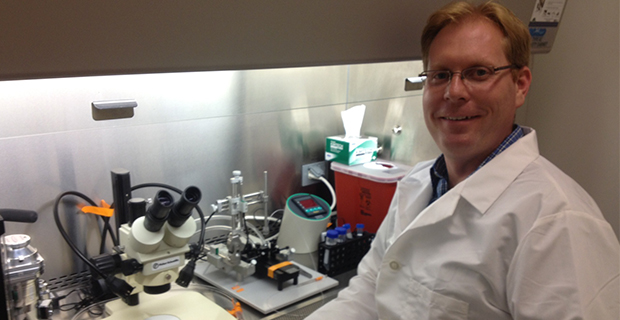 Brad Morrison smiling with hood and microscope in background