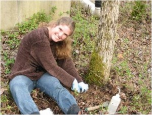 Dr. de Graaff posing for photo while digging next to tree trunk