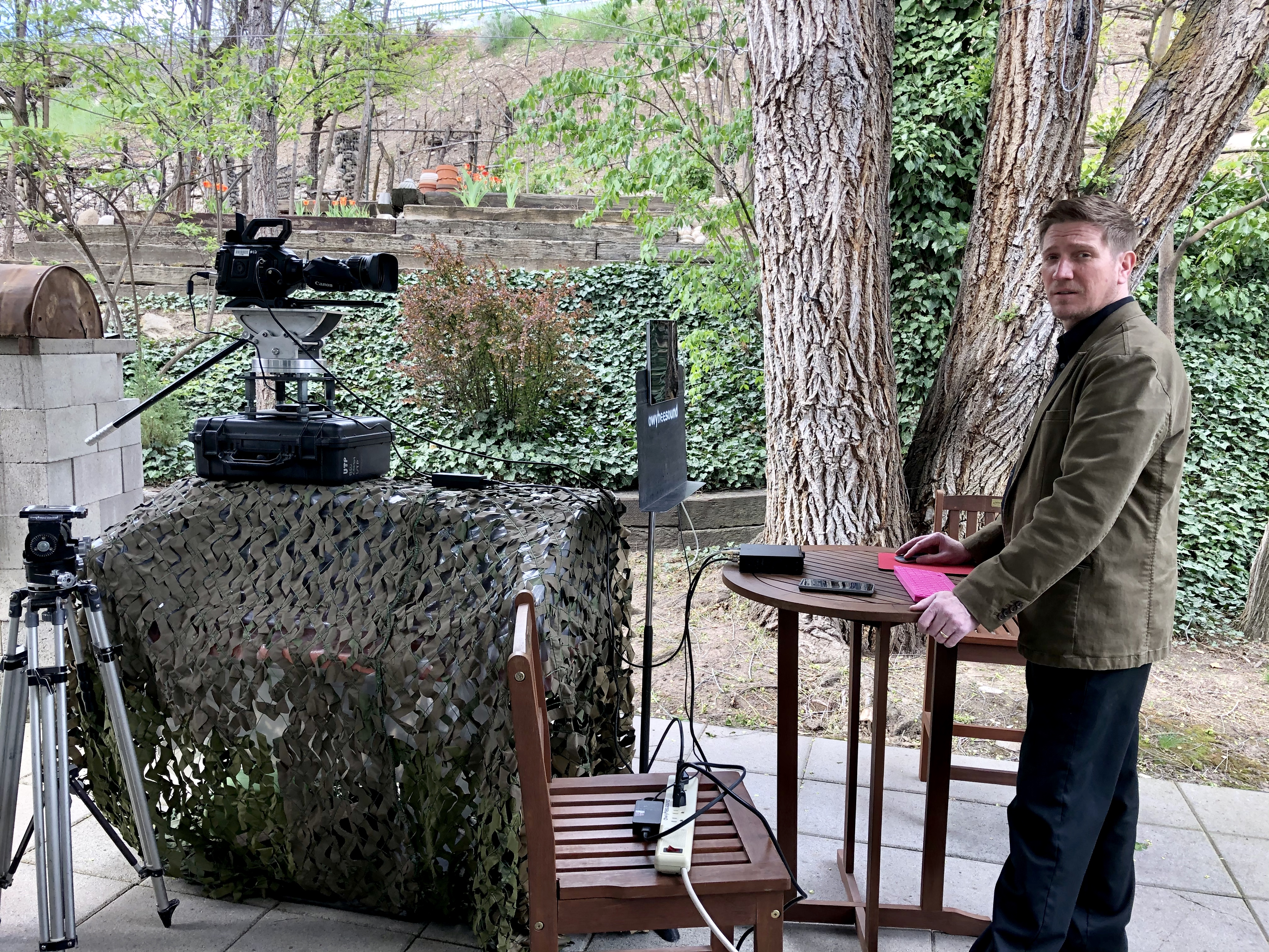Nathan Snyder next to studio set-up including camera, tripod, mouse, and screen.