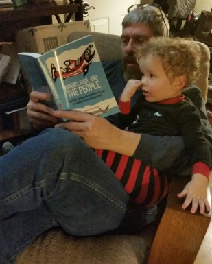 """alt=""""Fisheries biologist Richard Edwards and grandson Keagan Johnson take a look at 'Rivers, Fish, and the People', edited by Pei-Lin Yu. Photo taken by BSU Anthropology Graduate Julia Edwards, January 2016"""""""