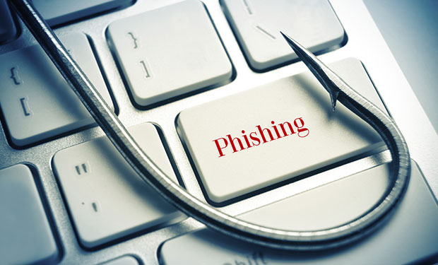 A fishing hook on top of a keyboard with the word Phishing on a key.