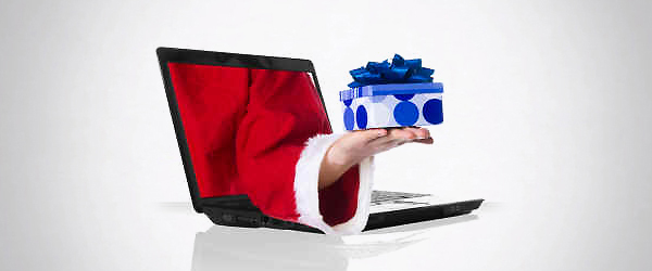 Santa handing a present through a laptop screen.
