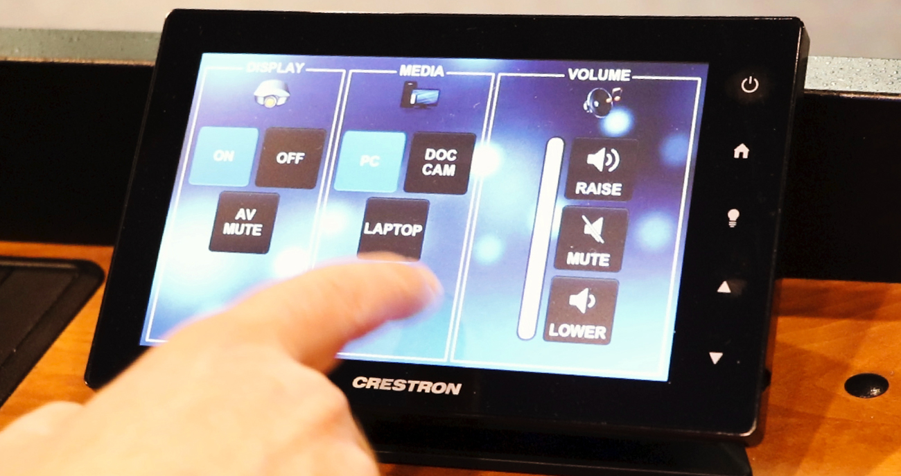 A hand taps the on button on the Crestron Control panel in a general classroom at Boise State