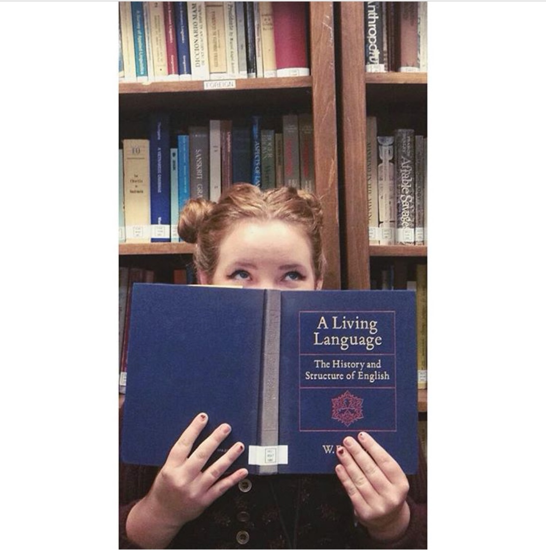 A student peeking over the top of a book