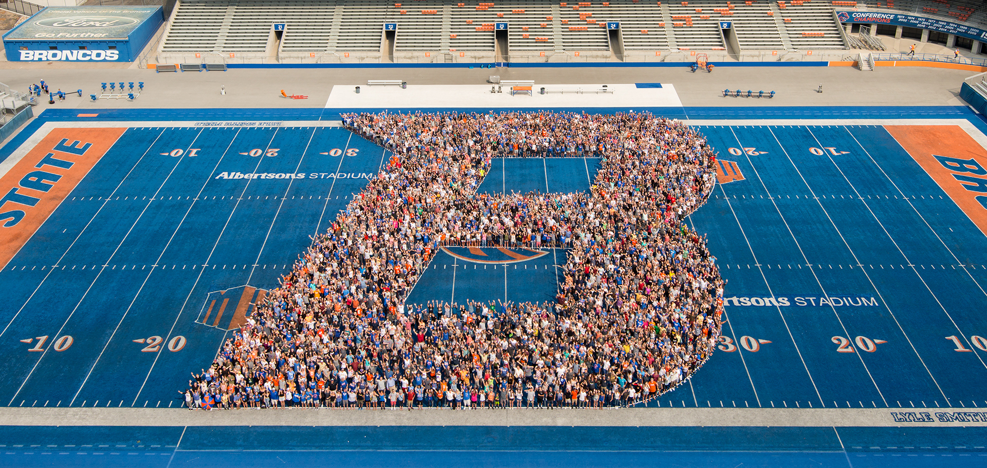 large group of students standing together to form the image of a B in the middle of the football field