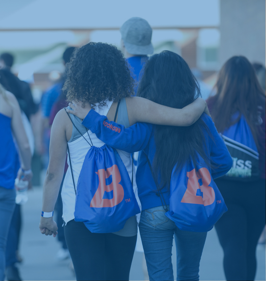 Two Students with Boise State bags and arms around each other