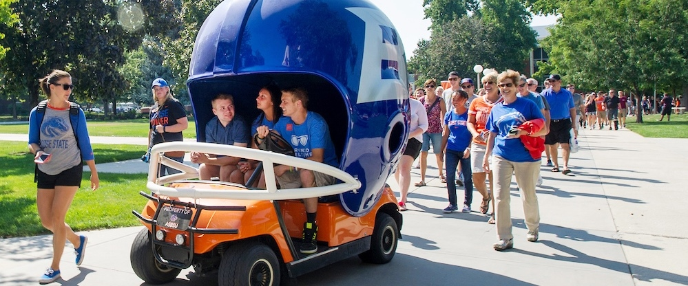 A group of students march behind a Boise State golf cart.