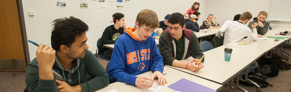 A group of three students working together in a classroom.