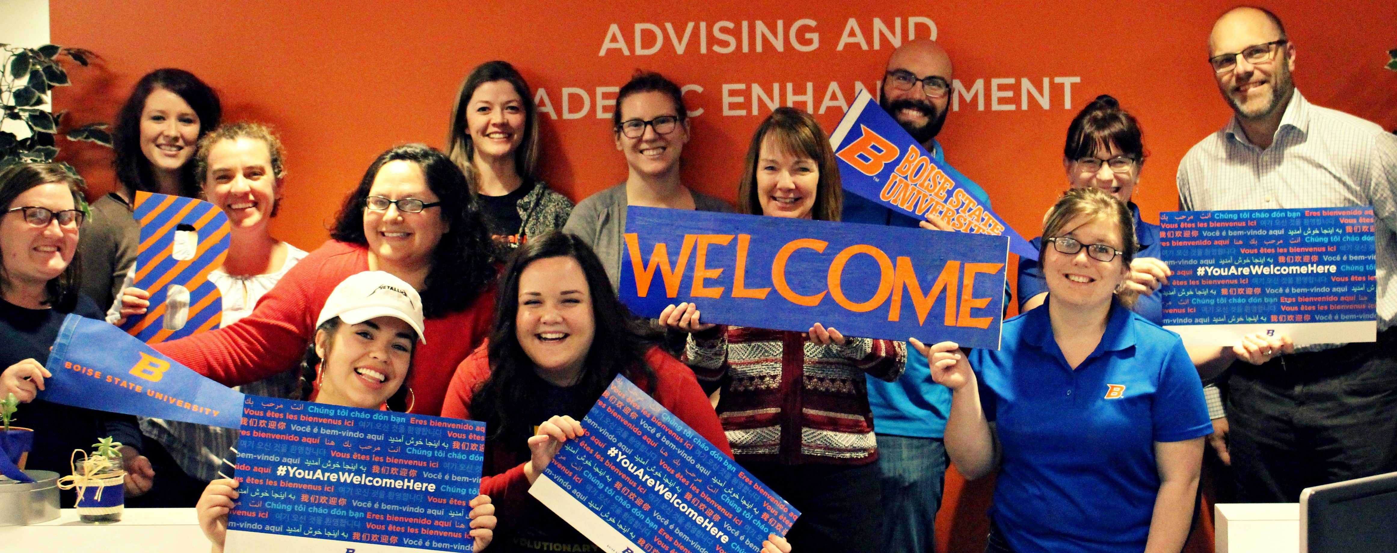 "AASC staff pictured together and holding ""You Are Welcome Here"" signs."
