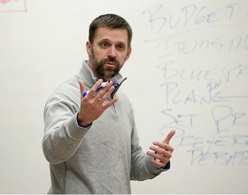 Professor lecturing in front of a whiteboard