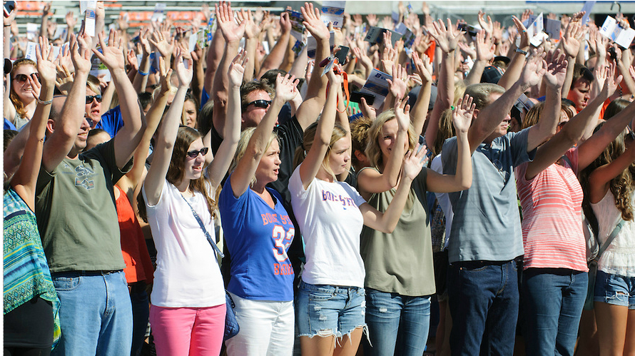 group of students and parents raising their arms