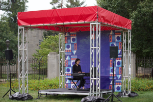 student playing on keyboard under a canopy