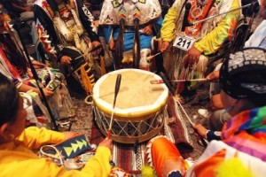Native American drum in middle of circle of people wearing traditional clothing