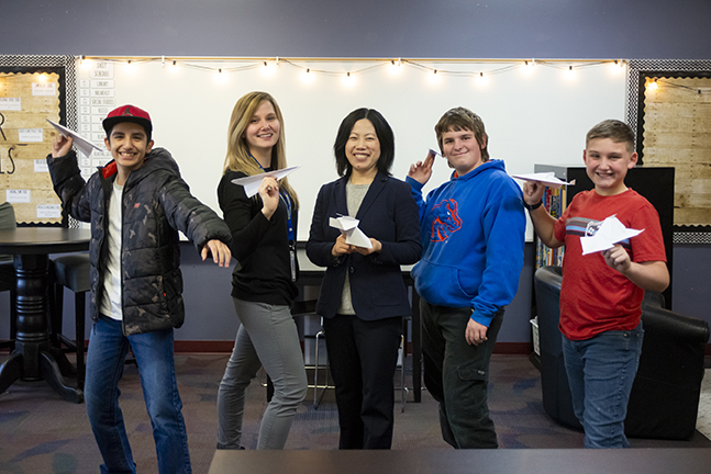 Photo of teachers with students holding paper airplanes
