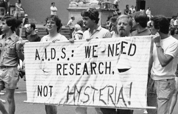 Marchers holding banner that says A.I.D.S: We Need Research Not Hysteria