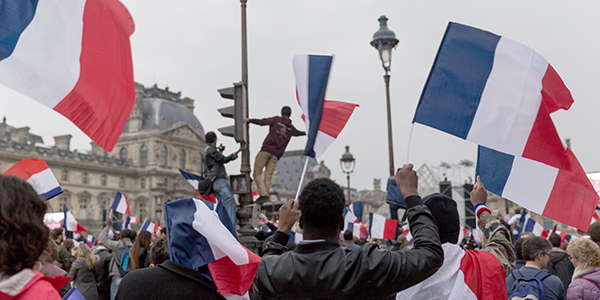 Photo of people waving french flags at a rally