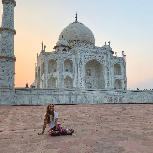 Student sitting in front of the Taj Mahal at sunset
