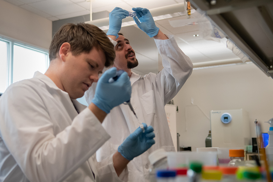 Gunes Uzer, assistant professor of Mechanical & Biomedical Engineering, works with students in a lab