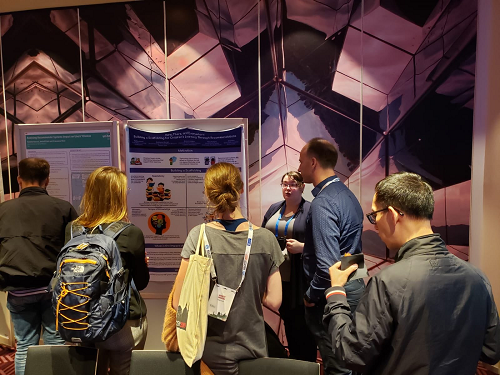 Photo of Ashlee presenting her research poster to several students at the RecSys conference