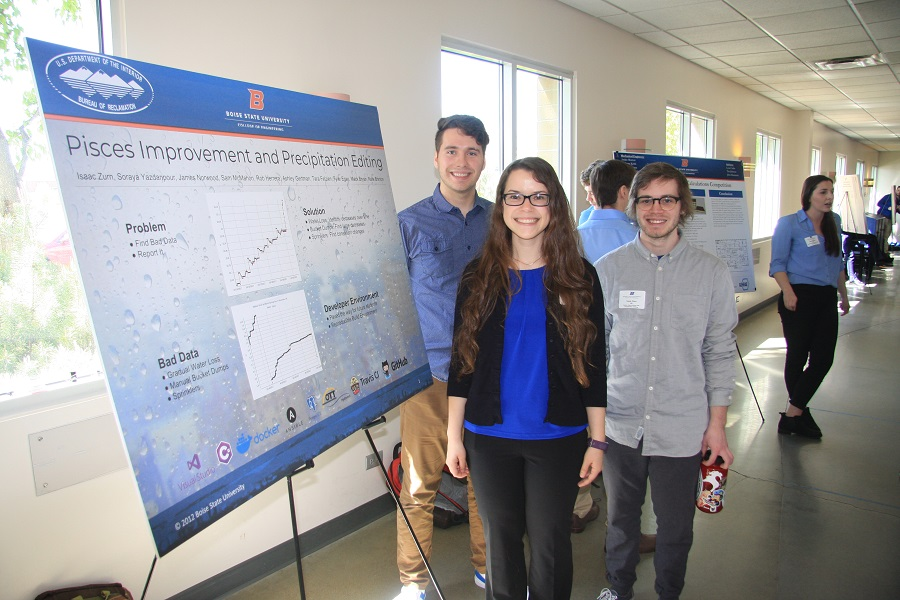 Photo of senior design team of three students standing next to their poster