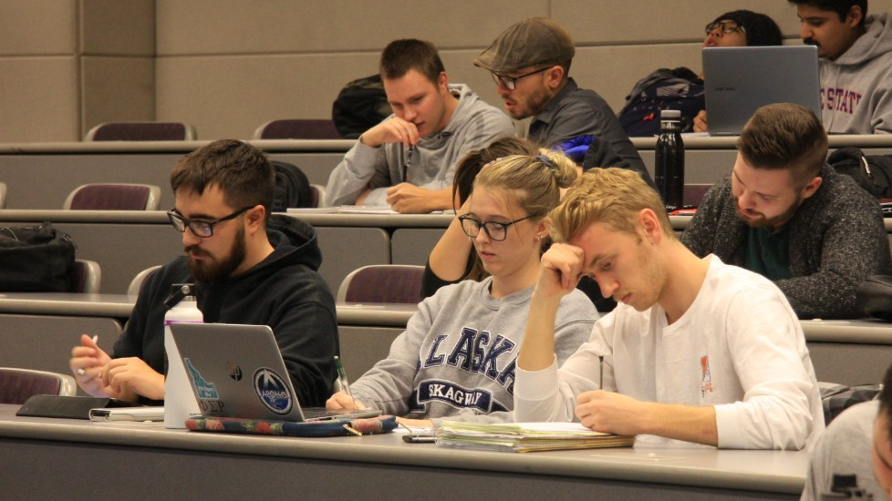 three students sitting in a lecture hall