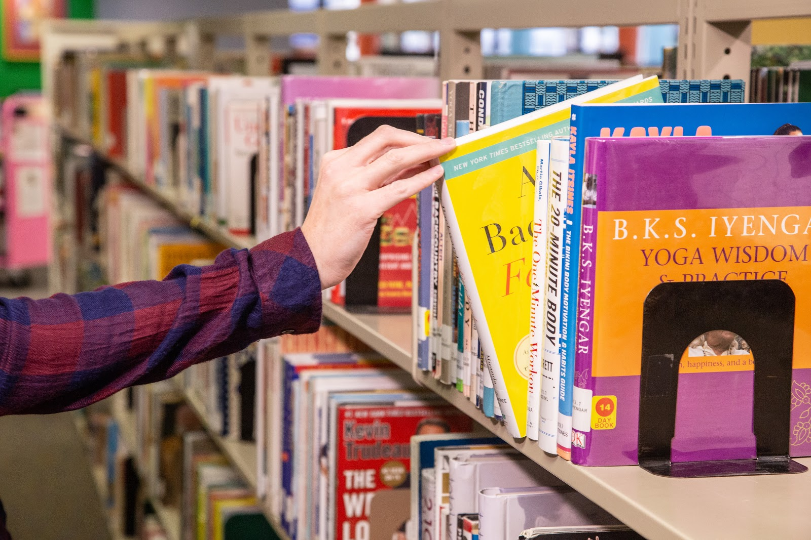 Person pulling book off library shelf