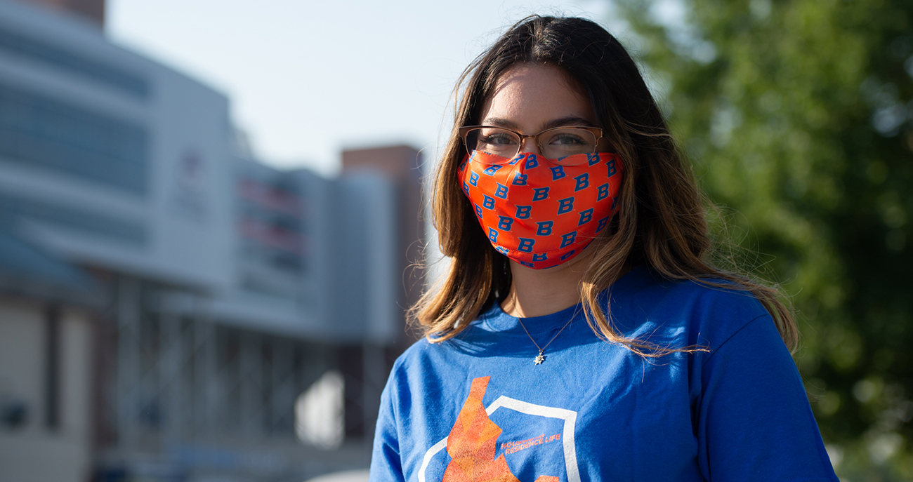 student in mask smiling